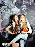 Back to school after summer vacations, two teen real girls in classroom with blackboard painted together, lifestyle Stock Photo