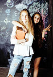 Back to school after summer vacations, two teen real girls in classroom with blackboard painted together Stock Images