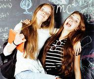 Back to school after summer vacations, two teen real girls in classroom with blackboard painted together, lifestyle Stock Photography