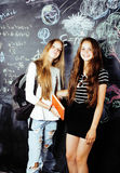 Back to school after summer vacations, two teen real girls in classroom with blackboard painted together Stock Photography