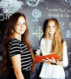 Back to school after summer vacations, two teen real girls in classroom with blackboard painted together, lifestyle Royalty Free Stock Images