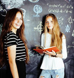 Back to school after summer vacations, two teen real girls in classroom with blackboard painted together, lifestyle. People concept close up Royalty Free Stock Photos