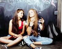 Back to school after summer vacations, two teen real girls in classroom with blackboard painted together, lifestyle Royalty Free Stock Photo