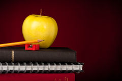 Back to school supplies. Stacked Books, school supplies, with an apple on top and a dark red background stock photography