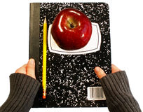 Back to school supplies. Child's hands holding back to school supplies: apple, pencil and notebook royalty free stock photography