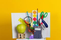Back to school supplies. Books and blackboard on yellow background Stock Photos