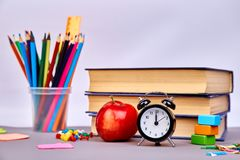 Back to school supplies. Books and red apple on green background. Still life with alarm clock. Copy space stock photography