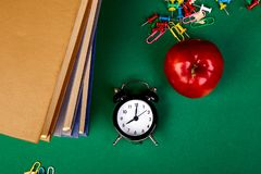 Back to school supplies. Books and red apple on green background. Still life with alarm clock. Flat lay. Top view. Copy space stock photo