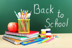 Back to school supplies. Books and blackboard. Stock Photography