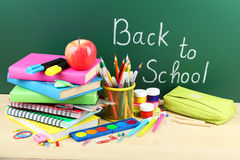 Back to school supplies. Books and blackboard. Royalty Free Stock Photos