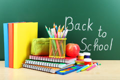 Back to school supplies. Books and blackboard Stock Photos