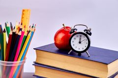 Back to school supplies. Books and red apple on green background. Still life with alarm clock. Copy space royalty free stock image