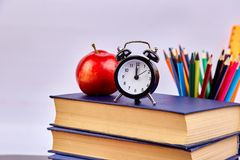 Back to school supplies. Books and red apple on green background. Still life with alarm clock. Copy space stock photo