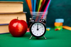 Back to school supplies. Books and red apple on green background. Still life with alarm clock. Copy space Royalty Free Stock Photo