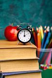 Back to school supplies. Books and red apple on green background. Still life with alarm clock. Copy space Stock Image