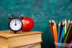 Back to school supplies. Books and red apple on green background. Still life with alarm clock. Copy space royalty free stock photography