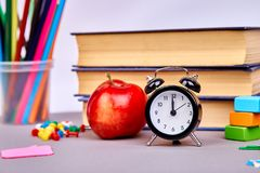 Back to school supplies. Books and red apple on green background. Still life with alarm clock. Copy space royalty free stock images