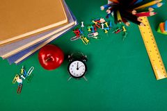 Back to school supplies. Books and red apple on green background. Still life with alarm clock. Flat lay. Top view. Copy space Royalty Free Stock Photography