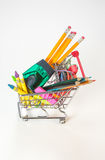 Back to School Supplies Concept. School supplies in a grocery cart on a white background Royalty Free Stock Images