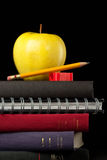 Back to school supplies isolated. Stacked books, school supplies, and an apple isolated on a black background stock photo