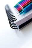Back to school supplies, multi colored pens and a spiral noteboo Stock Photo