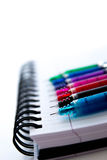 Back to school supplies, multi colored pens and a spiral noteboo Royalty Free Stock Image
