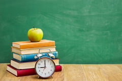 Back to school supplies. Over green  school blackboard Stock Image