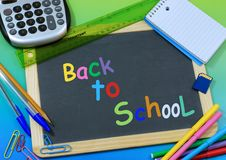 Back to School. School supplies surround a blackboard with colorful back to school message. Supplies include a calculator, ruler, notepad, memory card, colored royalty free stock photography