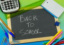 Back to School. School supplies surround a blackboard with colorful back to school message. Supplies include a calculator, ruler, notepad, memory card, colored stock photo