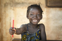 Back To School Symbol - African Girl Toothy Huge Smile Showing R. Ed Pencil. Little African girl holding pen as an educational symbol Stock Images