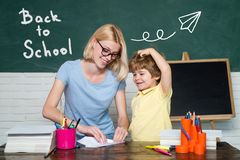 Back to school. Teacher helping kids with their homework in classroom at school. Kids from primary school. stock photography