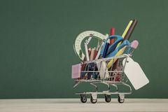Back to school template with multiple stationery in shopping trolley Stock Photos