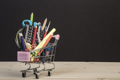 Back to school template with multiple stationery in trolley over black Royalty Free Stock Photo