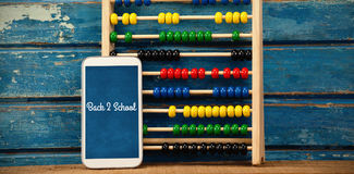 Composite image of back to school text against white background. Back to school text against white background against abacus with smart phone on table vector illustration