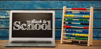 Composite image of back to school text against white background. Back to school text against white background against laptop by abacus on table royalty free illustration