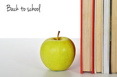 Back to school. Text, an apple and books Stock Photography
