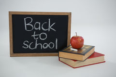 Back to school text with apple and books on white background. Close-up of back to school text with apple and books on white background Royalty Free Stock Images