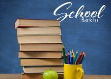 Back to School text on blackboard and Books on Desk foreground. Digital composite of Back to School text on blackboard and Books on Desk foreground Stock Photos