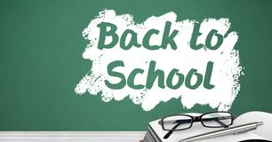 Back to school text on blackboard with glasses and book on desk Royalty Free Stock Photography