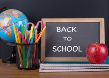 Back To School text on a blackboard with school supplies stock photography