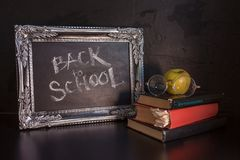 Back to school, text on chalkboard and a stack of textbooks. Textured vintage frame on a dark textured background. royalty free stock photo