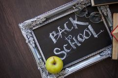 Back to school, Text on chalkboard in a vintage frame, and a textbooks royalty free stock image