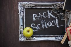 Back to school, Text on chalkboard in a vintage frame, and a textbooks royalty free stock photos