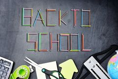 Back to school text from colorful pencils on chalkboard with border of school supplies Stock Photos