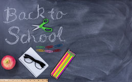 Back to school text on erased chalkboard with student supplies Royalty Free Stock Photo