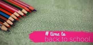 Composite image of back to school text with hashtag. Back to school text with hashtag  against close-up of multi colored pencils arranged Stock Image