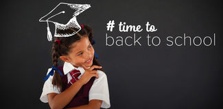 Composite image of back to school text with hashtag. Back to school text with hashtag against schoolgirl standing against blackboard in classroom Stock Photos