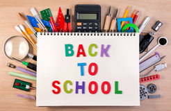 Back to school text on notebook over school supplies or office s Stock Photography