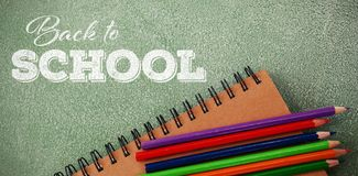 Composite image of back to school text over white background. Back to school text over white background against high angle view of spiral notebook and pencils Royalty Free Stock Photography