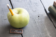 Back to school text and pencil and apple on the table. Back to school idea - text, yellow pencil and green apple on the table Stock Image